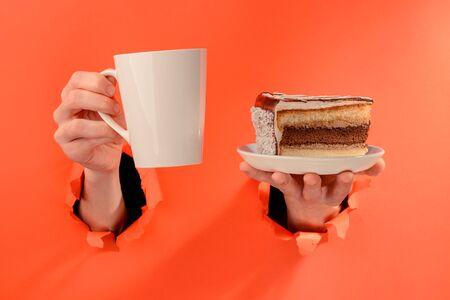 Hand holding a mug of coffee and a piece of chocolate cake