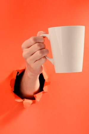 Hand holding a blank cup of coffee through a torn hole in red paper