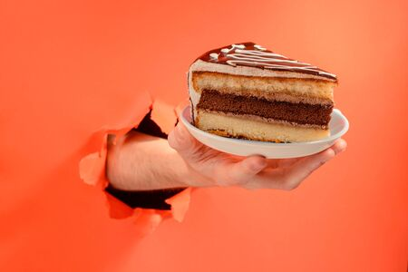 Hand serving a chocolate cake through a torn hole in red paper background. Banco de Imagens