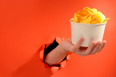 Hand holding a whole cup of potato chips through a torn hole in red background Banco de Imagens