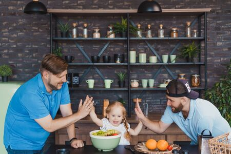 Gay parents cooking with their little daughter and giving high fives