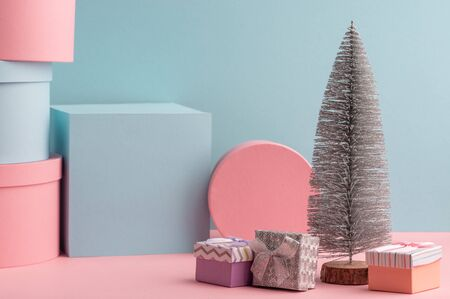 Mini fir tree and various gift boxes on pink and teal background