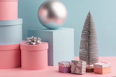 Fir tree, ball, round and square gift boxes on pink and teal background