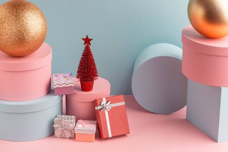 Pile of various gift boxes, balls and Christmas tree on turquoise background