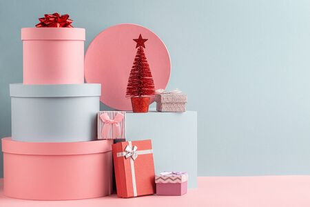 Pink and turquoise round gift boxes and red fir tree on teal background