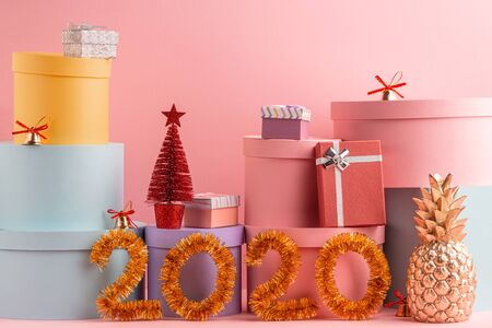 Pile of gift boxes, fir tree and tinsel 2020 numbers on pink background Stock Photo