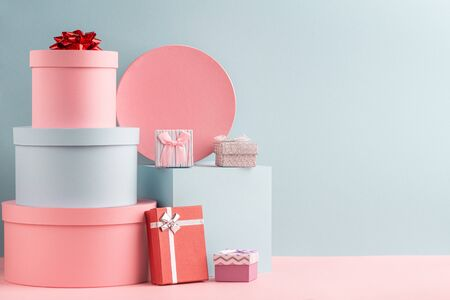 Pink and turquoise round gift boxes and red fir tree on teal background Фото со стока - 134781930