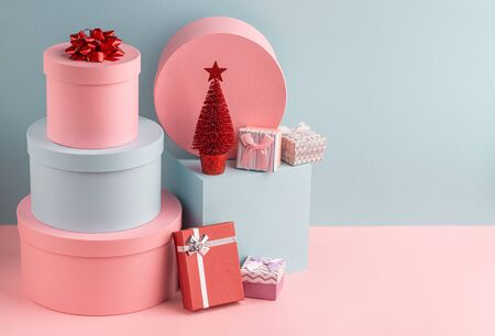 Pink and teal gift boxes and red Christmas tree on turquoise background