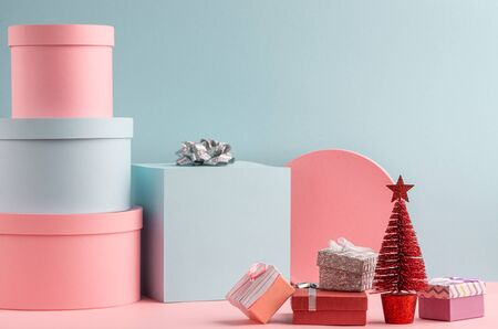 Pink and teal gift boxes and red fir tree on turquoise background Stock Photo
