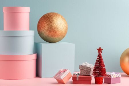 Teal and pink gift boxes, red Christmas tree and golden balls