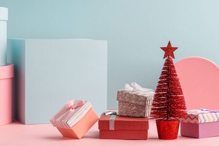 Red Christmas tree and pile of gift boxes on turquoise background Stock Photo