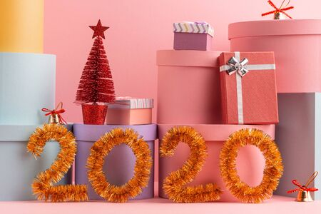 Happy New Year 2020 greeting card with gift boxes on pink background
