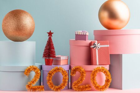 Pile of gift boxes, balls, Christmas tree and tinsel numbers on teal background