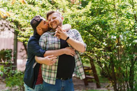 Gay couple in the park. Young man hugging and kissing his boyfriend