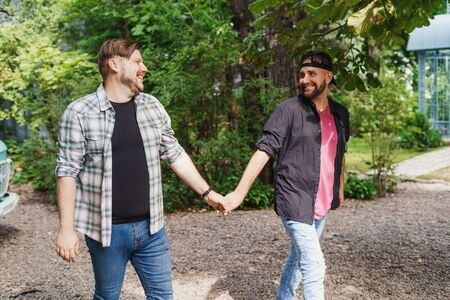 Two adult gay men walking, holding each others hands