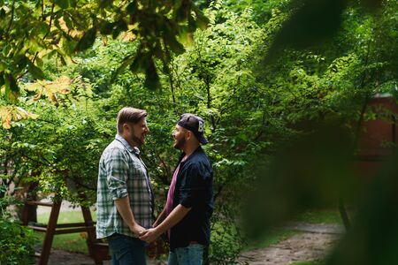 Beautiful gay couple in the park. Two adult men holding each others hands