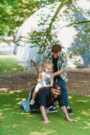 Gay couple play with their child in the backyard 写真素材