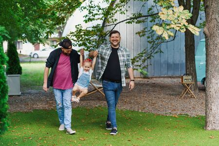 Gay couple walking with their child in the park 写真素材