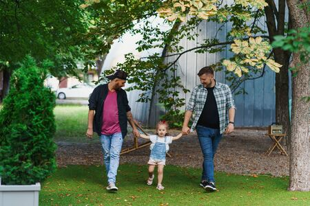 Gay family walking with a little daughter in the park
