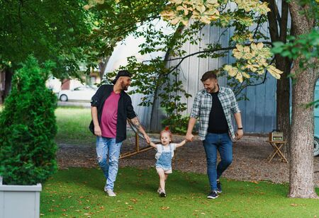 Gay couple walking with adopted child in the park