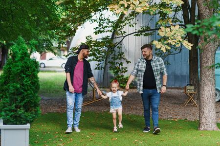 Beautiful gay couple with their child walking in the park