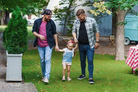 Gay couple with little daughter walking in the park Stock Photo