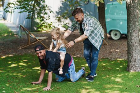 Family having fun in backyard. Cheerful gay fathers playing with daughter