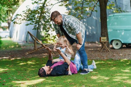 Gay family playing in backyard. Cheerful dads and their little daughter