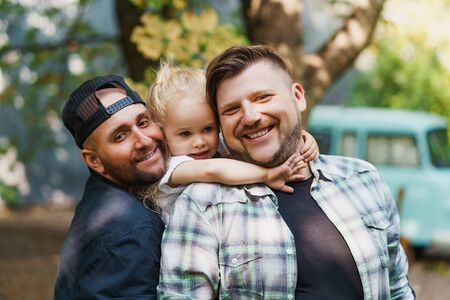 Gay family with little daughter. Two adult men posing with their adopted child