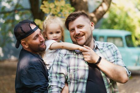 Portrait of proud gay parents and their child