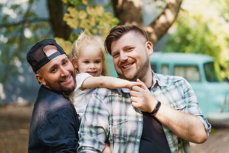 Portrait of happy gay family with little daughter