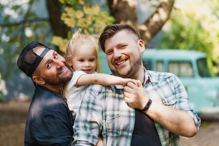 Beautiful gay family with a daughter. Fathers posing with their little princess 写真素材