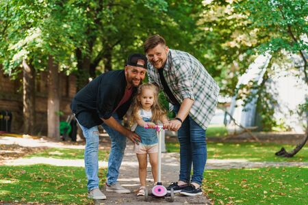Portrait of gay parents and their little daughter in the park