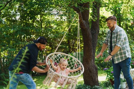 Fathers swinging their daughter on a hammock chair