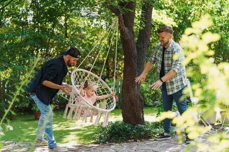 Daddies swinging their baby on a hammock chair