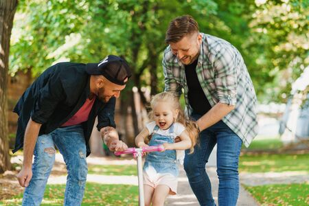 Portrait of gay parents with daughter in the park