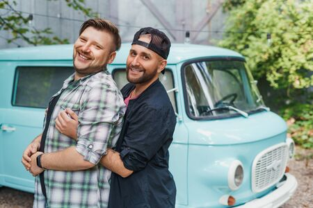 Portrait of a gay couple in front of an old-fashioned car van 写真素材