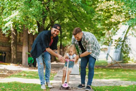 Happy gay parents and their child in the park