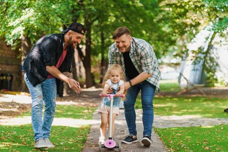 Cheerful gay parents and their child in the park