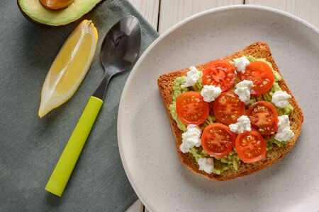 Delicious toast with avocado, tomato and ricotta on white plate, top view. Simple and tasty vegetarian food. Reklamní fotografie