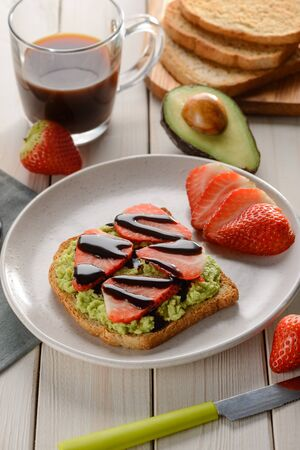 Toast with avocado, strawberries, chocolate and cup of coffee. Good vegan breakfast as a great day starter.
