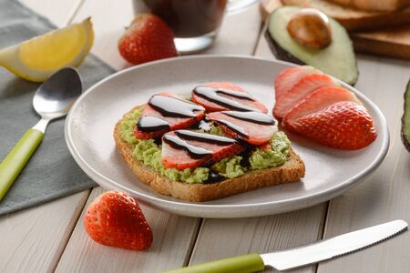 Mashed avocado, strawberry and chocolate syrup. Nice combination for a toast top. Sweet and healthy food.