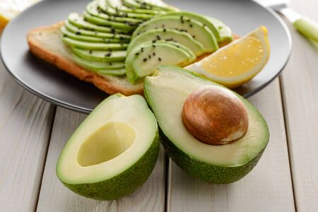 Halves of avocado and toast. Simple and healthy alternative snack Reklamní fotografie