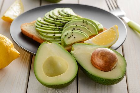 Avocado halves and toast with slices. Ingredients on white wooden table