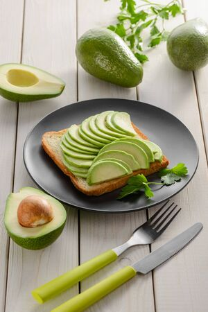 Toast with avocado slices, sesame seeds and parsley on black plate. Healthy meal served with fork and knife on wooden table. Reklamní fotografie