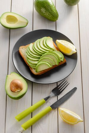 Toasted bread with avocado slices and lemon on black plate. Healthy breakfast meal served with knife and fork. Reklamní fotografie