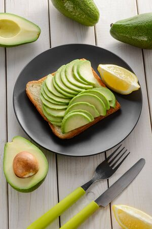 Toast with green avocado slices and lemon juice. Healthy snack on black plate, top view.