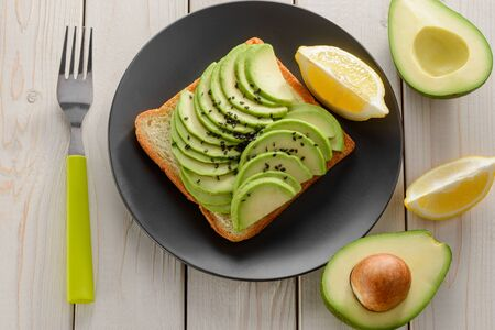 Toast with avocado slices. Top view on a vegetarian snack