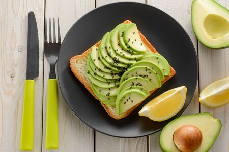 Avocado toast served with ingredients and cutlery on white table, top view. Tasty and healthy food for a lunch.