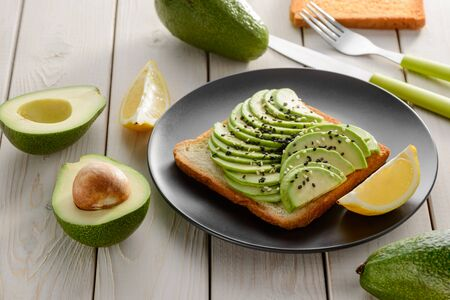 Avocado toast with sesame seeds and lemon. Tasty snack on black plate and its ingredients on white wooden table.